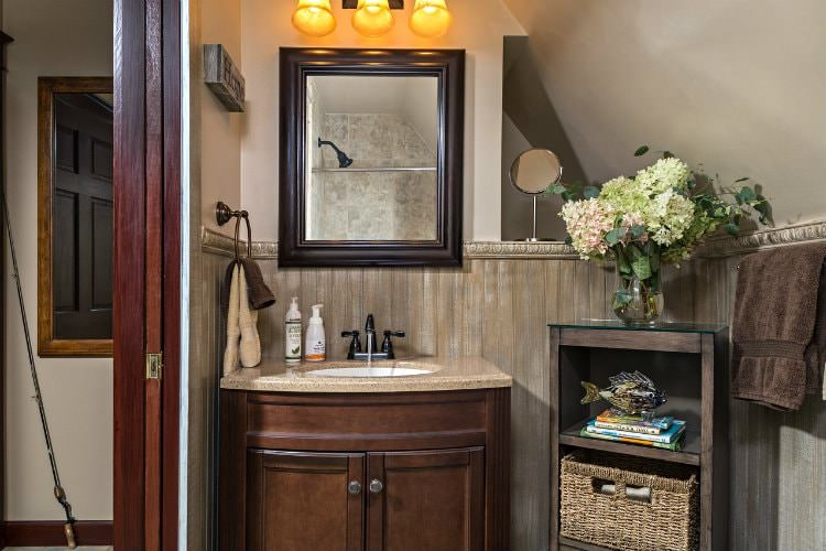 Rustic guest bathroom with wooden vanity, a wooden plank chair rail, and tan walls.