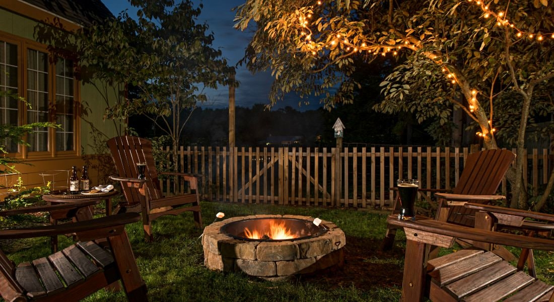 Cozy outdoor setting at nighttime, wooden lawn chairs surrounding a stone fireplace, twinkle lights in the trees
