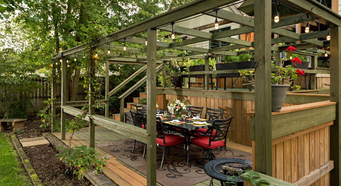 A wooden back porch dining area covered by a wooden Catalina surrounded by green foliage