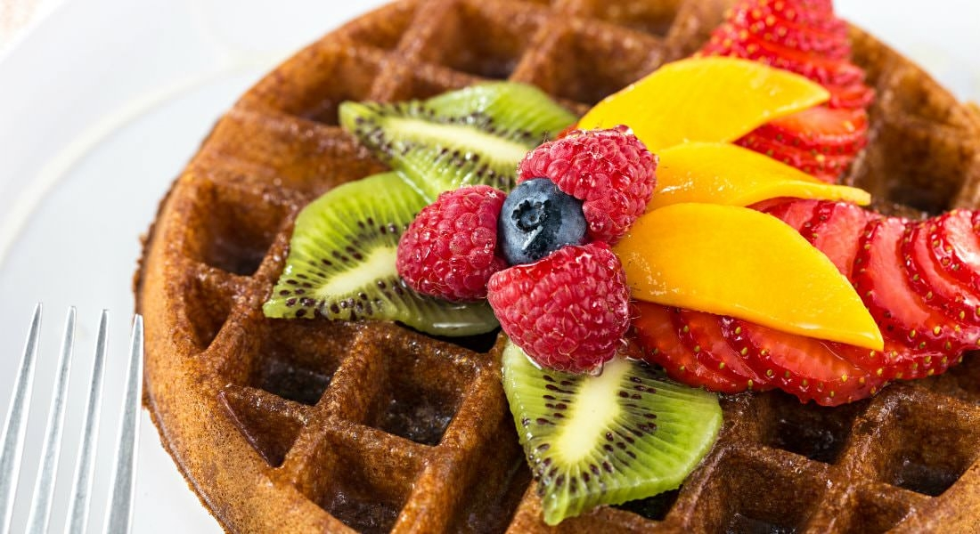 A beautifully golden waffle with a spread of fresh vibrant fruit including bright red strawberries
