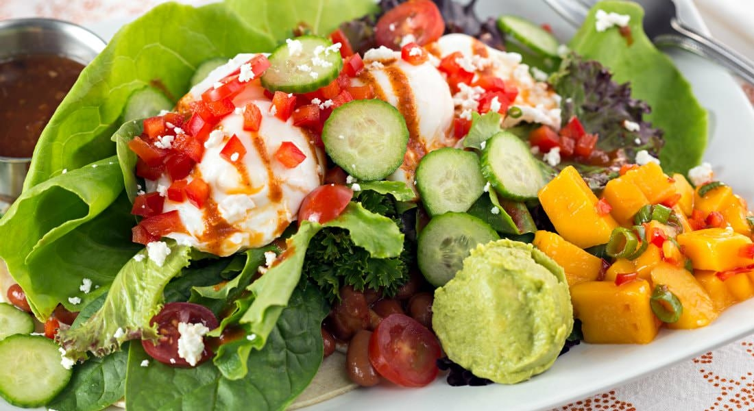 A vibrant mixed salad with an array of green vegetables, toped with guacamole and tomatoes