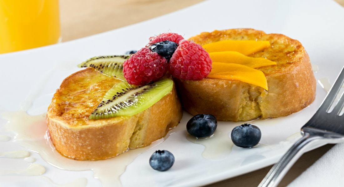 A plate of two lightly browned French toasts with fresh fruit and syrup on top.