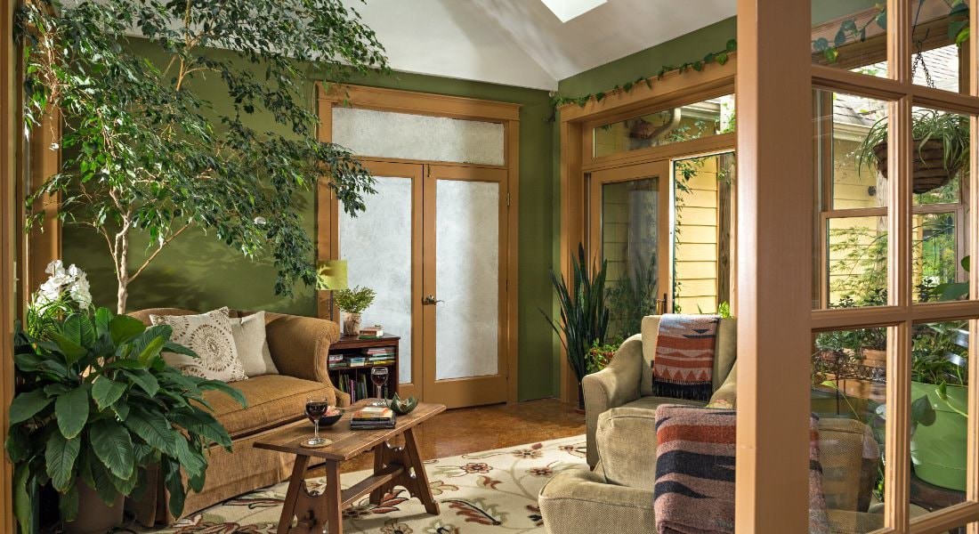 A seasonal room with glass doors, a large area carpet, and several tan cushioned seating options.