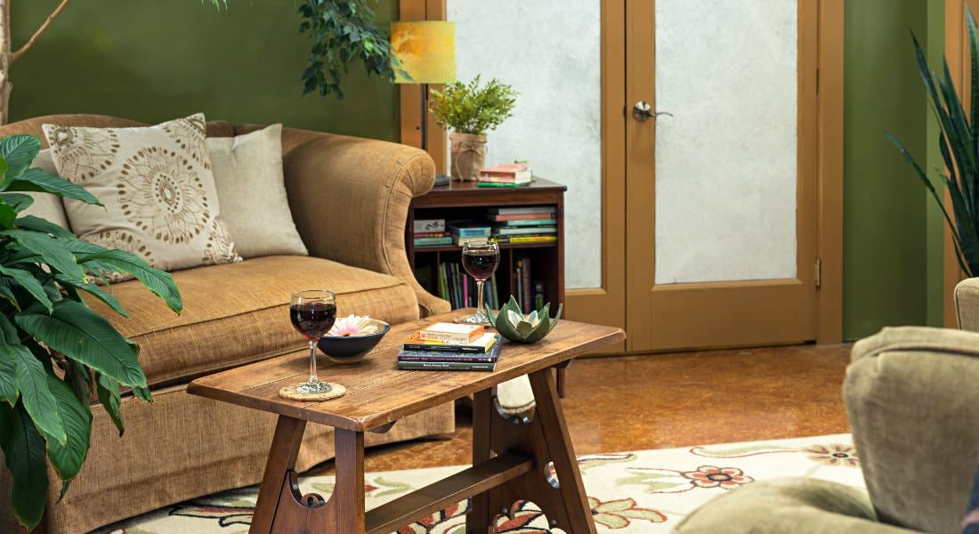 Seasonal room with a brown cushioned couch with a wooden table in front, holding two glasses of red wine.