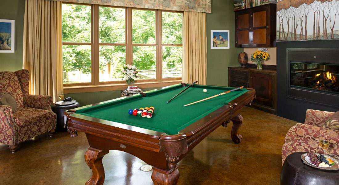 Interior room with a wooden pool table with green felt covering, two red floral chairs and a fireplace.