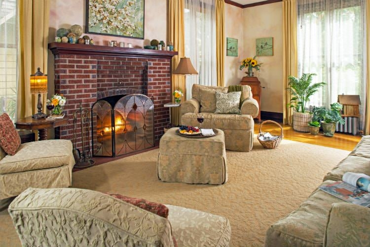 A bright sitting room with several floor to ceiling windows, a brick fireplace, and large tan area rug