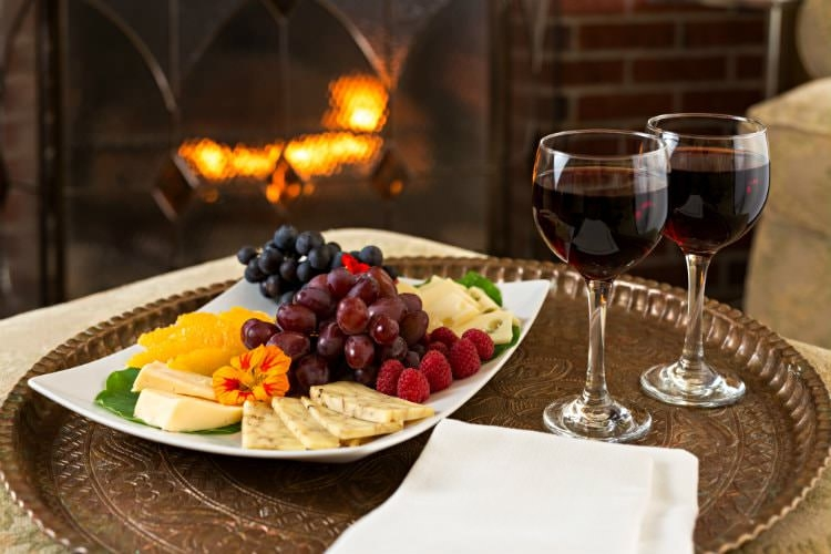 A bronze platter topped with a fruit and cheese spread and two glasses of red wine