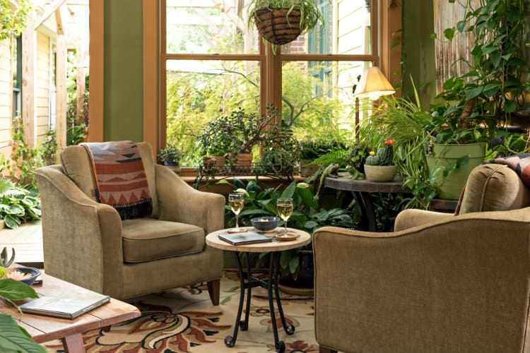 An indoor outdoor room with two tan cushioned chairs surrounded by many green plants.