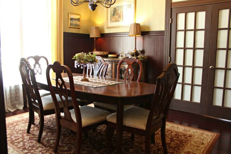 A nice wooden dining table in a room with a pair of brown French doors and a large window.