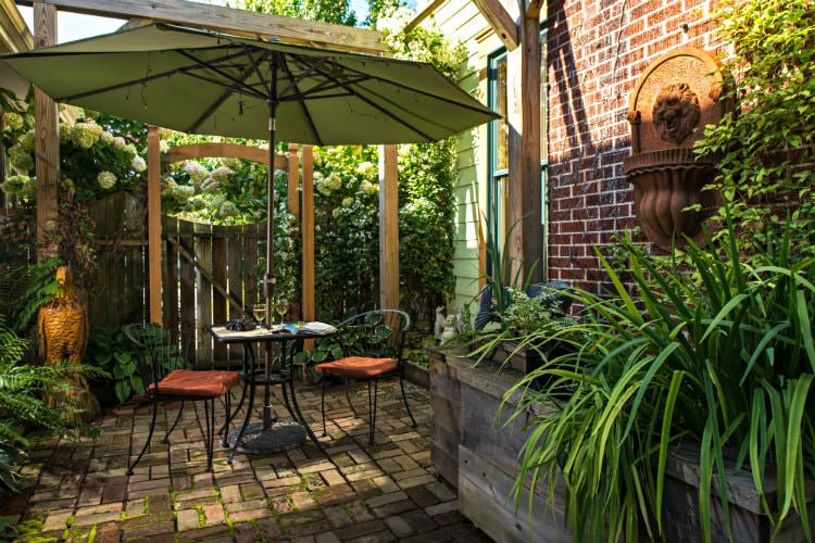 Outdoor area with brick pavement, a sitting table with an umbrella and two glasses of white wine