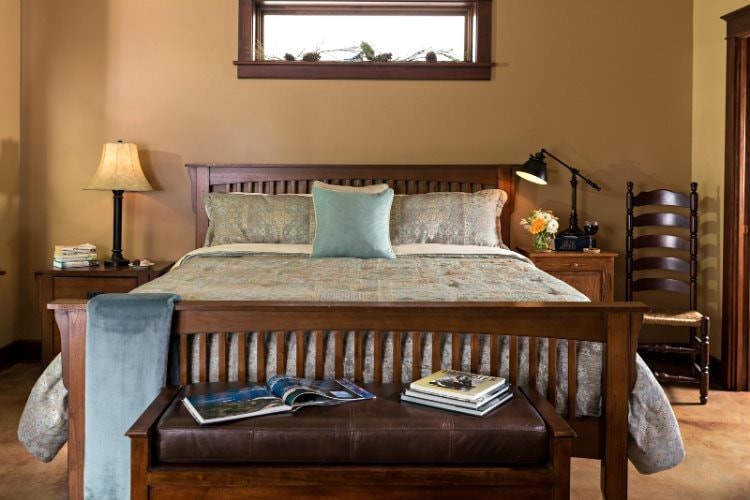 Guest room with light brown walls, pale teal bedding and two nightstands with reading lights.
