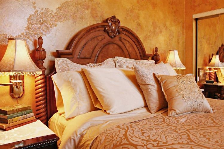 Guest room with floral print painted walls, floral pattern cream bedding and two nightstands
