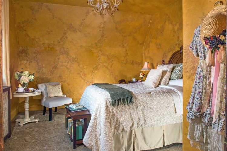 Guest bedroom with golden artistically printed walls, grey carpeted flooring, and cream bedding.