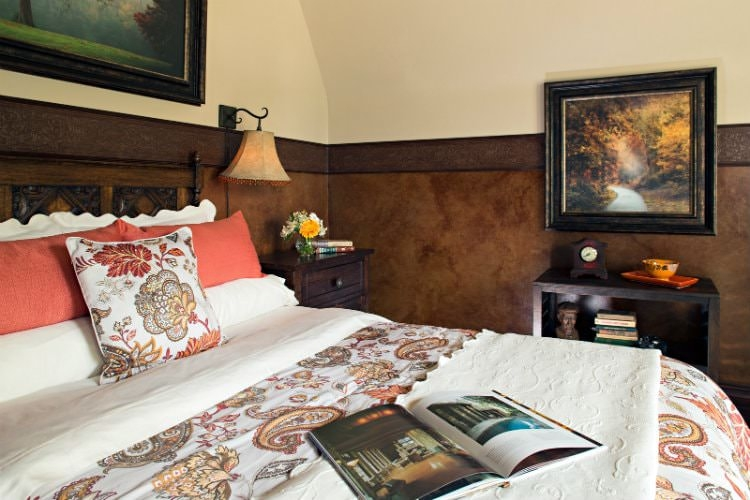 Paisley bedding in a cream guest room with beautifully framed artwork and wooden side tables.