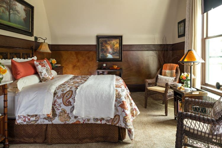 Guest room with tan carpeted flooring, paisley bedding, a chair rail with artistic wallpaper and several reading lamps.