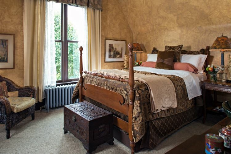 Guest room with brown paisley bedding, a brown wooden chest at the foot of the bed, large window with drapes.