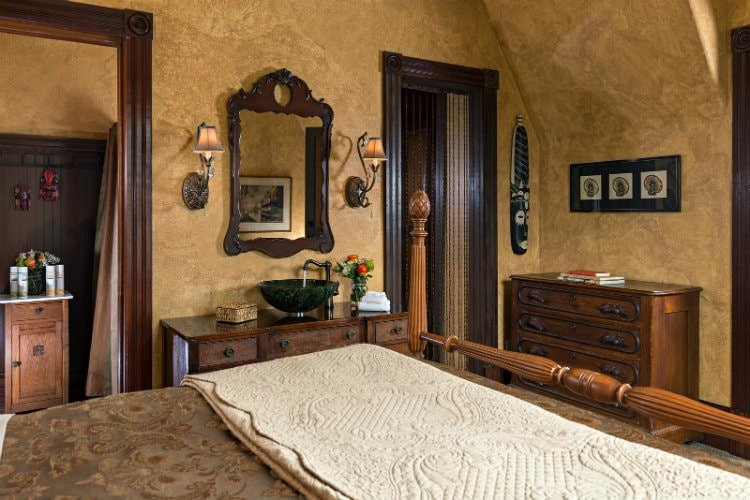 Guest room with Victorian influenced décor, a wooden vanity and wardrobe.