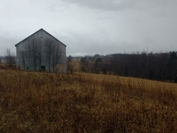 Midwinter barn in barren field with cloudy sky