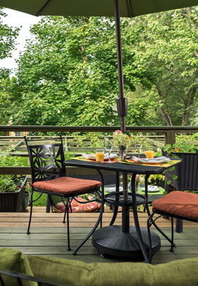 Table on deck overlooking the green back yard