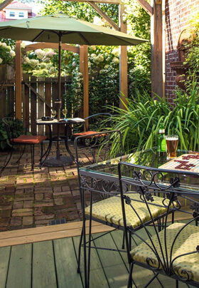 Courtyard with plants, metal tables and chairs and umbrella