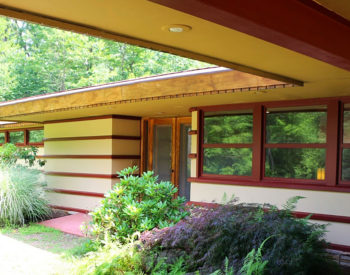 Mid-Century Modern home with rust colored window sashes and tan walls. Rhododendrons and other landscaping