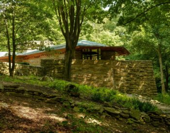 Usonian stone house in a woodland setting with trees and grasses.