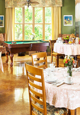 Room with dining tables and pool table.