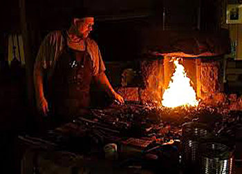 Blacksmith standing at firey forge