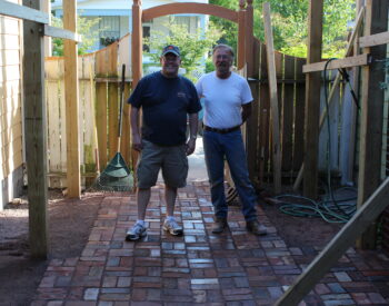 brick courtyard with two men working