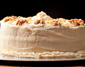 A round two-layered cake with a thick white icing and sprinkled on top with nuts.