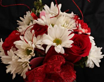 A gorgeous bouquet of red and white flowers in a glass vase