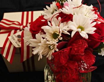 A gorgeous bouquet of red and white flowers in a glass vase, a red and white present to the side,