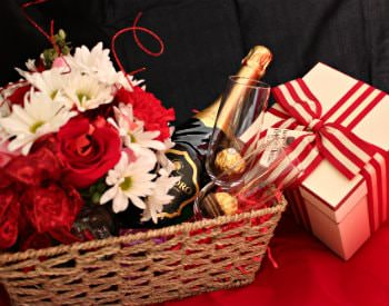 A tan wicker basket holding two wine glasses, a bottle of wine, a bouquet of flowers and a present