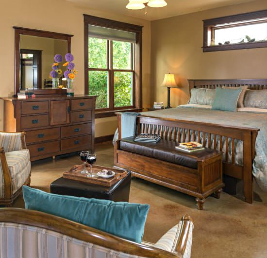 Tan guest bedroom with a shiny pale teal bedding, carpeted flooring, and large wooden vanity