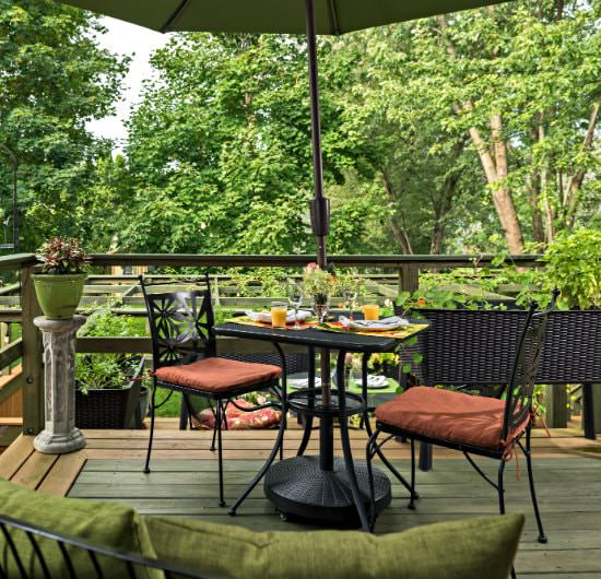 Outdoor wooden porch with a black table covered by a large green umbrella displaying a breakfast spread
