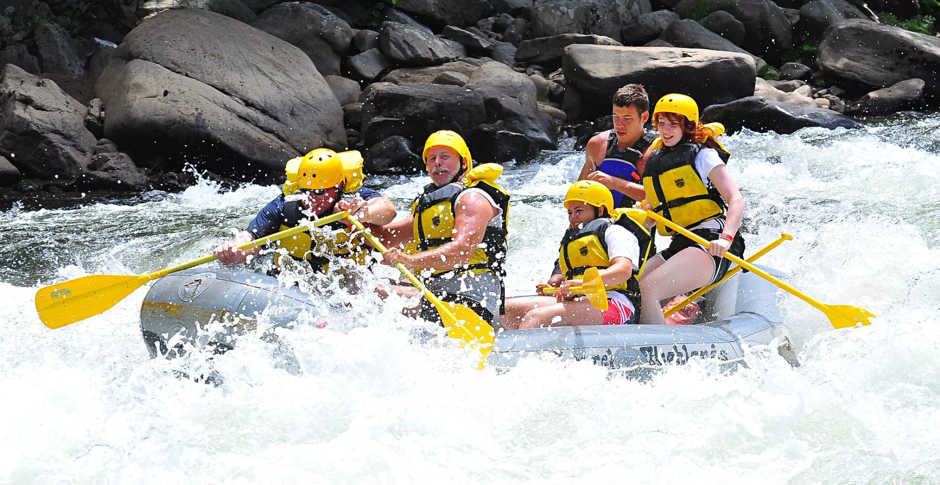 A grey river raft going down strong river rapids with a group of people wearing yellow safety garb