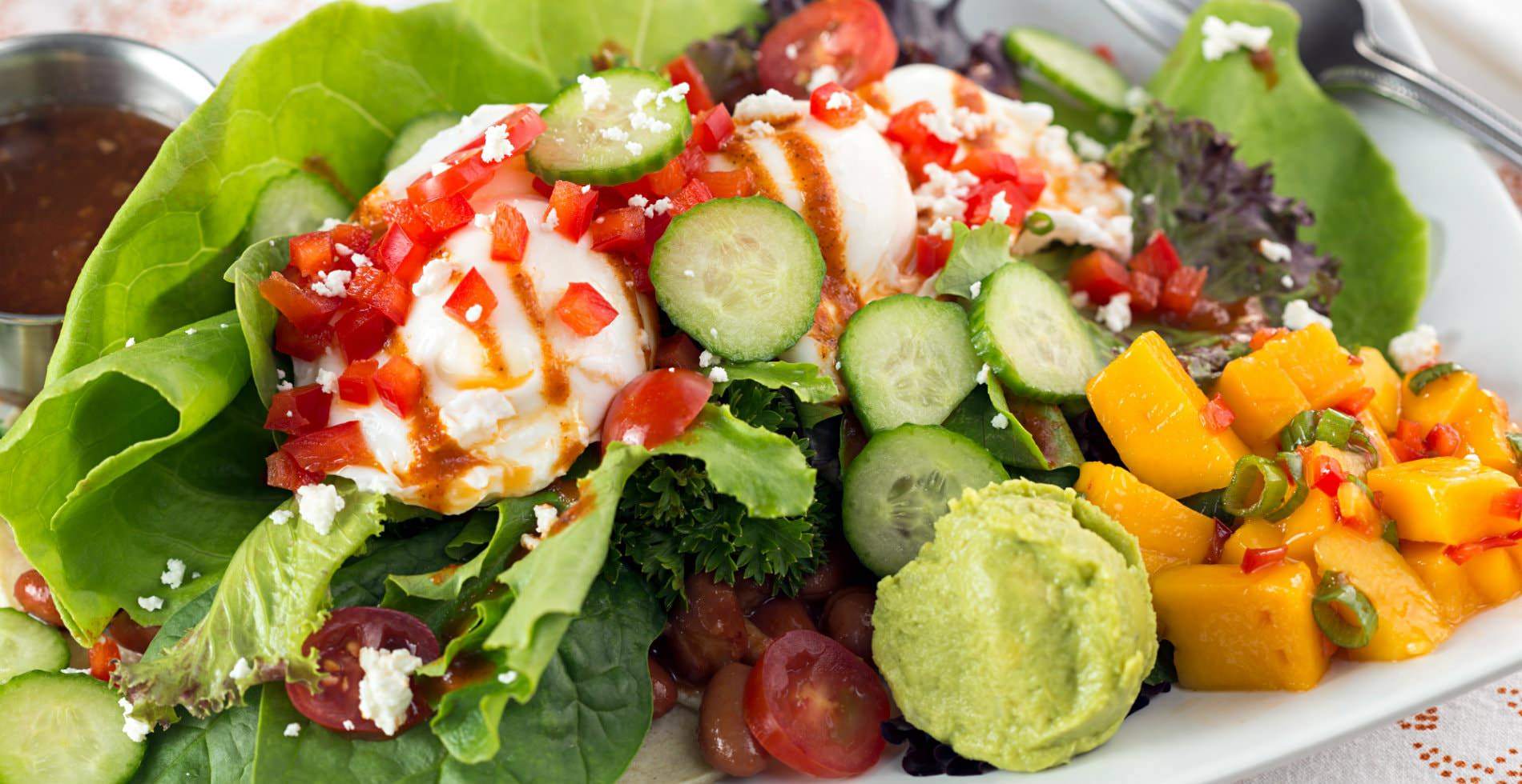 vibrant mixed salad with an array of green vegetables, topped with guacamole and tomatoes