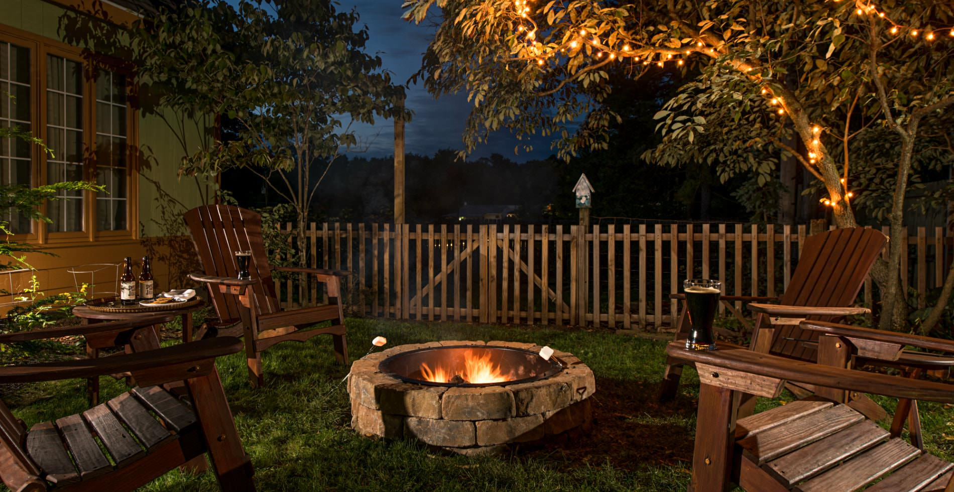Cozy outdoor setting at nighttime, wooden lawn chairs surrounding a stone fireplace, twinkle lights in the trees,