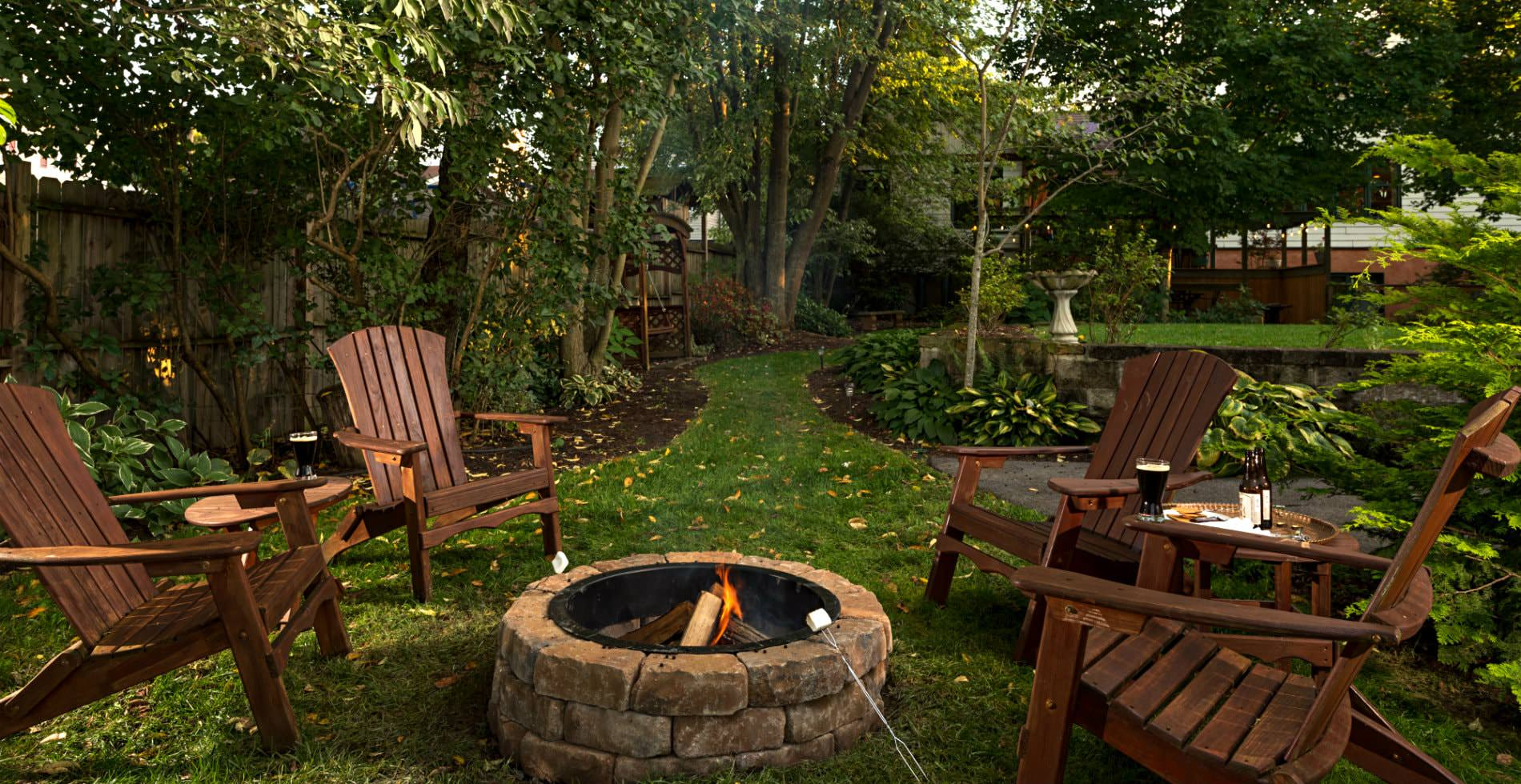Outside view of a grassy backyard, several lawn chairs around a stone fireplace, a green path leading away from scene
