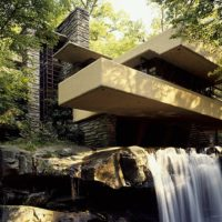 A modernized grey stone building built at the edge of a waterfall and stream, surrounded by thick foliage and bushes