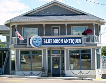 exterior view of Blue Moon Antiques, a grey two story building with white detailing on a street with an incline