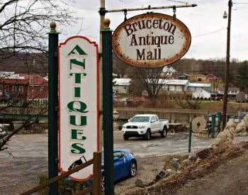 "Exterior view during winter time of a wooden sign which says ""Bruceton Antique Mall"""