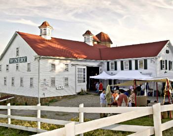 Exterior view of Christian Klay Winery, a white building with red roofing, surrounded by a white picket fence
