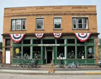 An exterior view of a vintage brick building with a green storefront on display, bikes parked in racks out front.