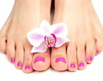 A pair of freshly manicured feet with bright pink toenail polish and a flower on top of the feet.