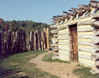 Exterior view of an old wooden lodge from Fort Necessity, surrounded by brown wooden stumps.