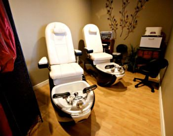 An interior view of a massage room, two white chairs with feet soaking tubs and taupe walls