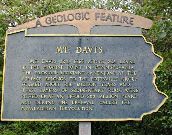 "A slate colored sign that says, ""A geologic feature, MT. Davis"", mounted on a wooden post surrounded by green shrubbery."