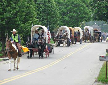 Street view of the National Road Festival, a line of covered wagons filled with people in old western outfits.