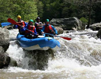 A blue river raft full of people going over a slight drop in a fast moving river